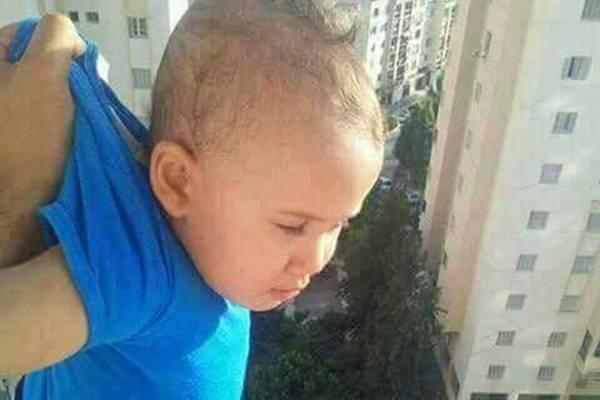 صورة مقربة للوضعية الطفل الخطرة من عمارة من 18 طابق